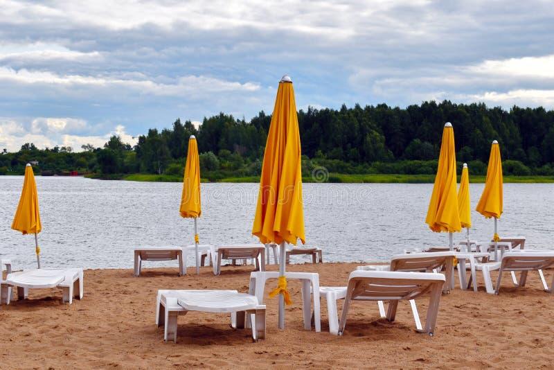 在海滩的太阳床与黄色伞在夏天 免版税库存照片