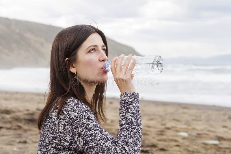 在海滩的女孩饮用水 库存照片