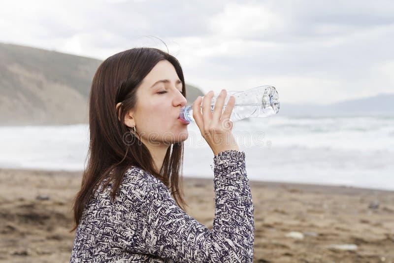 在海滩的女孩饮用水 免版税库存照片