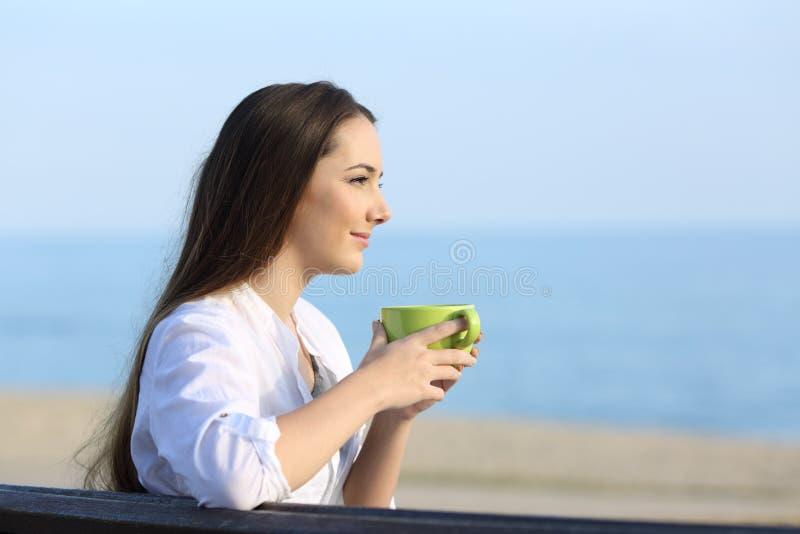 在海滩的妇女放松的饮用的咖啡 库存图片