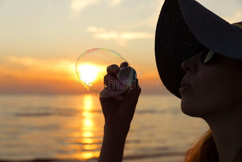 在海滩的妇女画象吹的肥皂泡 美丽的太阳 库存图片