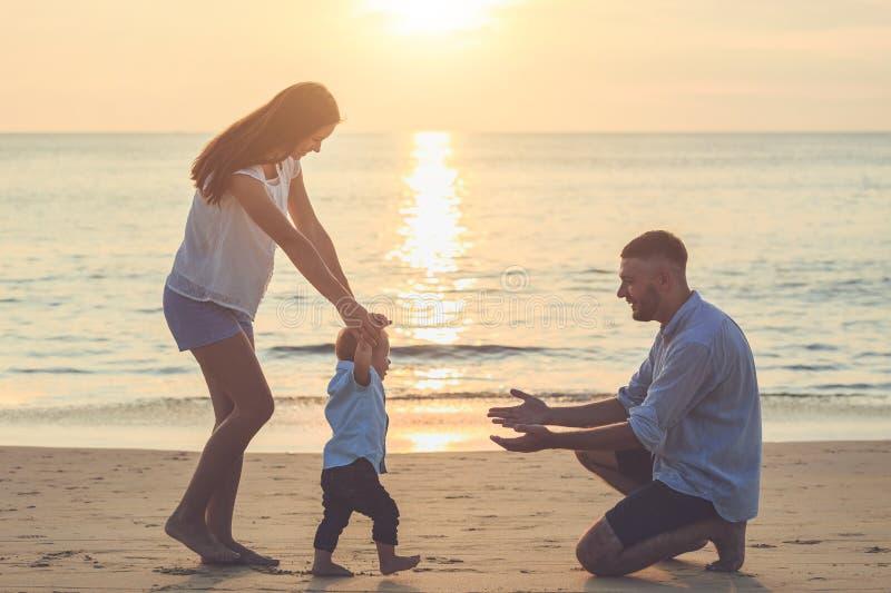 在海滩的家庭,握她儿子和走的手的母亲, 免版税库存照片