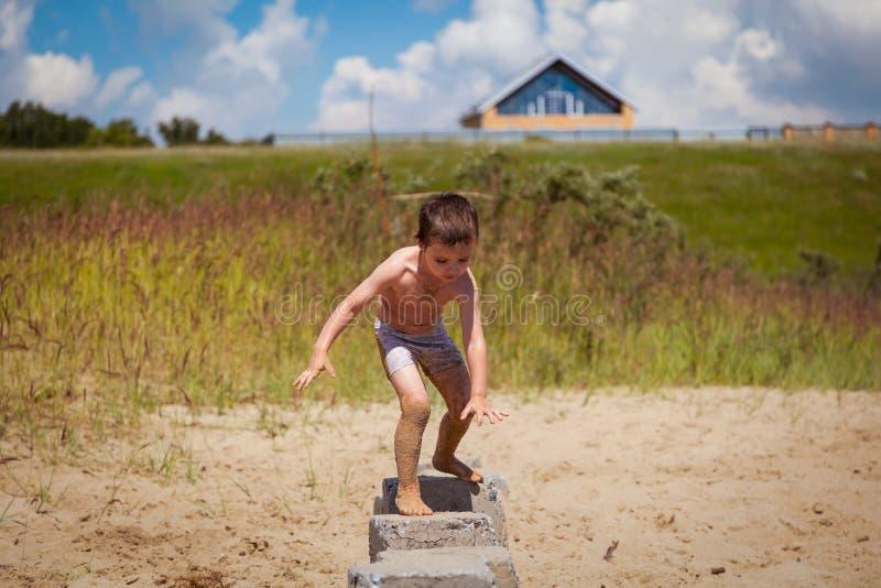 在海滩的小深色头发的男孩步行 免版税库存照片