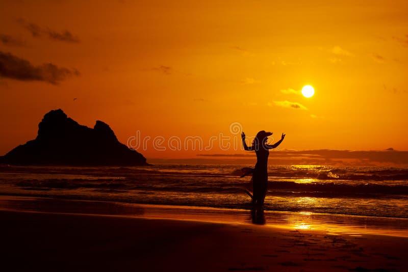 在海滩的少妇剪影在夏天 免版税库存图片