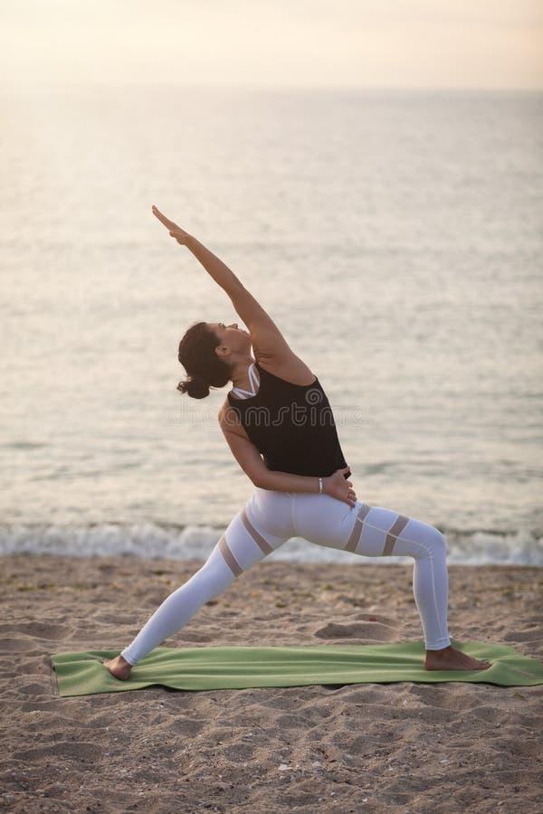在海滩的少妇实践的瑜伽 反向战士姿势, Viparita Virabhadrasana 户外体育 健康生活 免版税库存图片