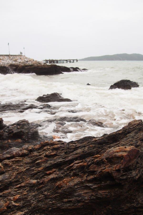 在海滩的岩石由海,当桥梁舒展入海和灯笼,在自然本底 免版税库存图片