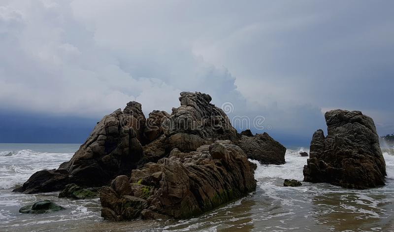 在海滩的岩石露出作为云彩滚动  库存图片