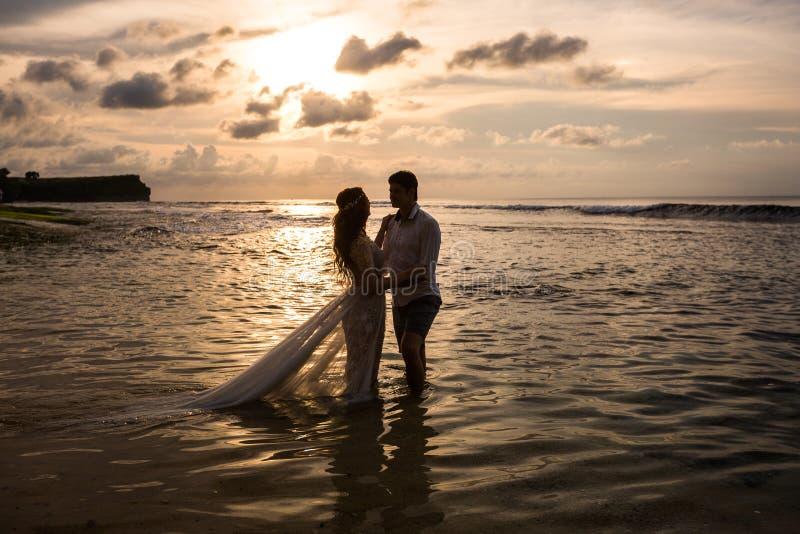 在海滩的年轻夫妇在日落 免版税库存图片