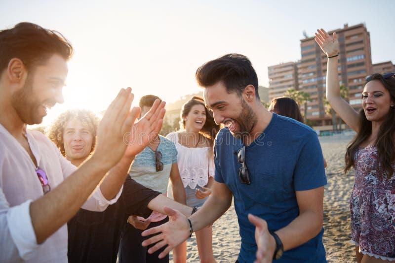 在海滩的年轻愉快的人跳舞与朋友 免版税库存照片