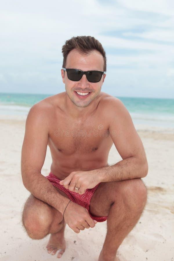 在海滩的微笑的蹲下的人身分 免版税库存照片