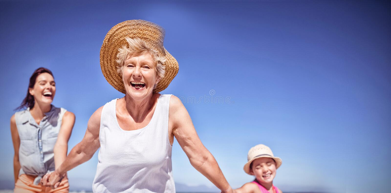 在海滩的快乐的多代的家庭 免版税库存照片