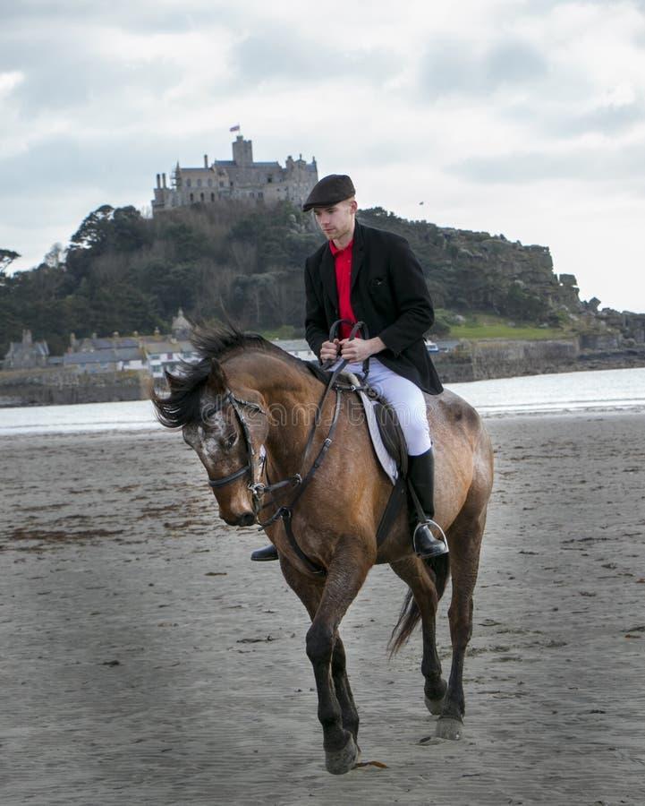 在海滩的悦目雄性马车手骑乘马在有圣迈克尔` s登上的传统骑马衣物在背景中 库存照片