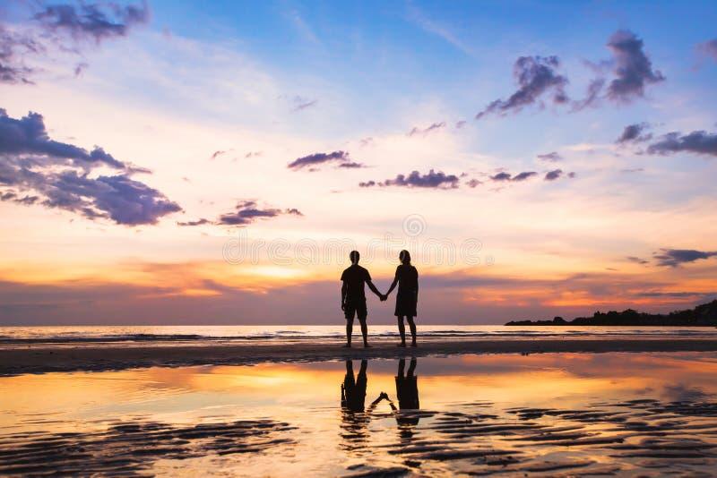 在海滩的愉快的夫妇家庭,剪影在日落的,男人和妇女 免版税图库摄影