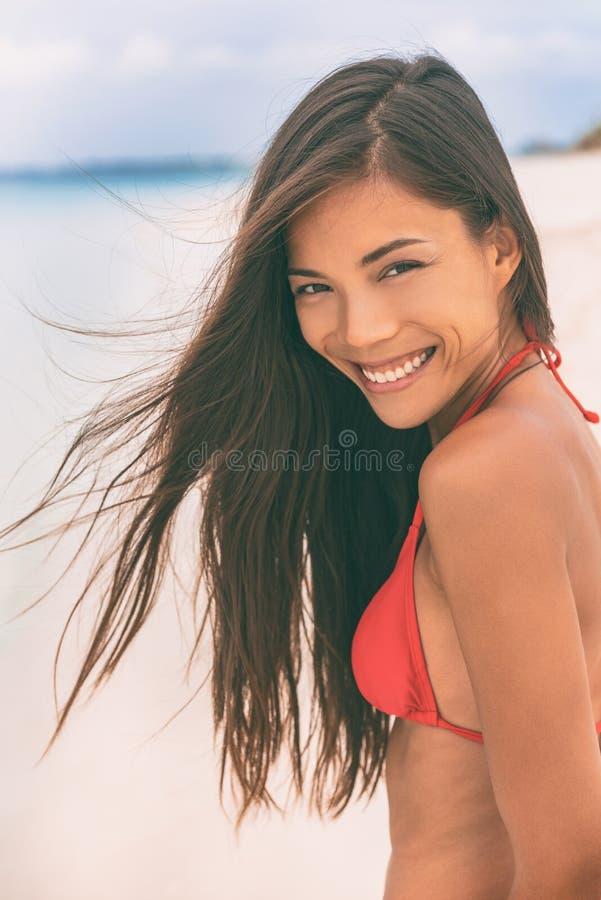 在海滩的愉快的微笑的年轻亚洲妇女在阳光下夏天休假 完善的牙微笑牙齿概念,健康中国女孩与 免版税库存照片