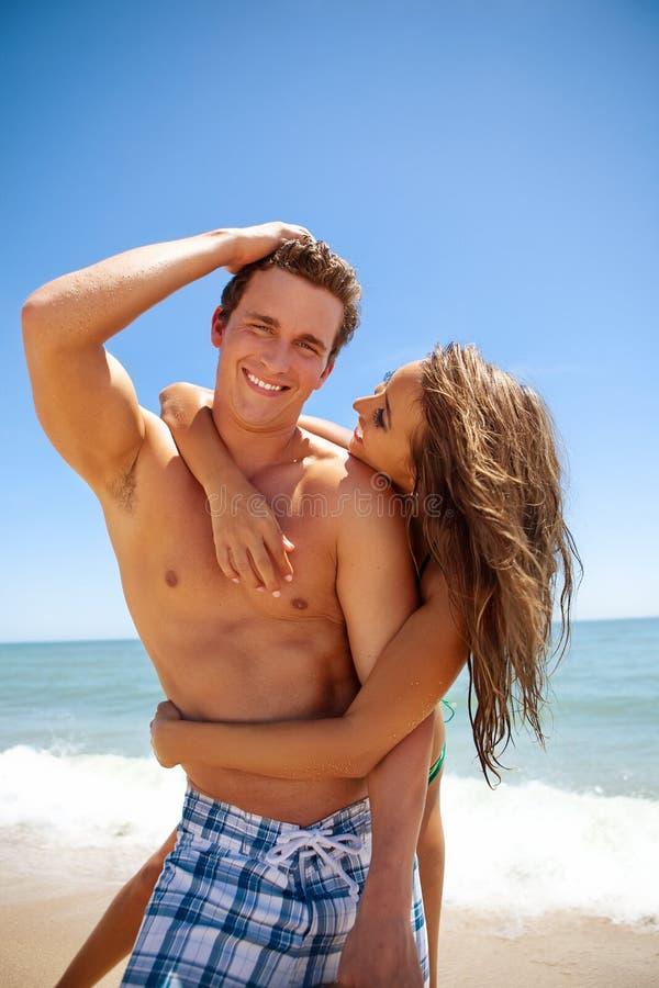 在海滩的愉快的新夫妇 库存图片