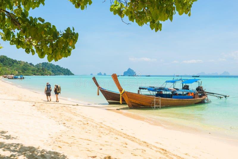 在海滩的旅游夫妇与在海的longtail小船在泰国 免版税库存照片