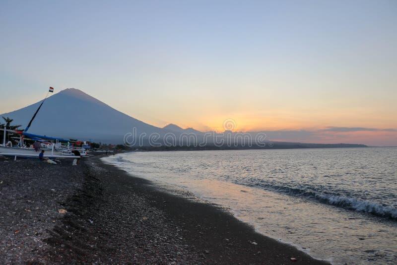 在海滩的日落在一个热带海岛上 桔黄色天空和云彩 在天际的大庄严火山 图库摄影