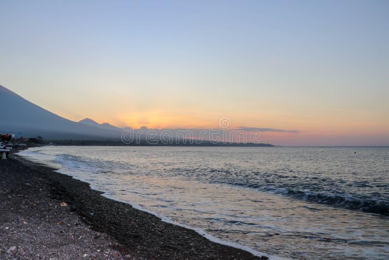 在海滩的日落在一个热带海岛上 桔黄色天空和云彩 在天际的大庄严火山 安静的海 库存图片