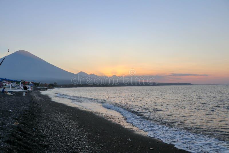 在海滩的日落在一个热带海岛上 桔黄色天空和云彩 在天际的大庄严火山 安静的海 免版税库存图片