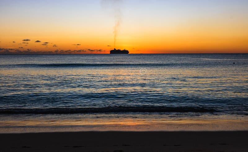 在海滩的日落在巴巴多斯岛,加勒比 在太阳前面被夺取的游轮,航行远离巴巴多斯港口 库存图片