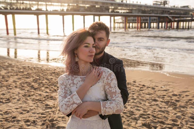 在海滩的日落期间在容忍的年轻和美好的已婚夫妇庆祝他们的婚礼 库存图片