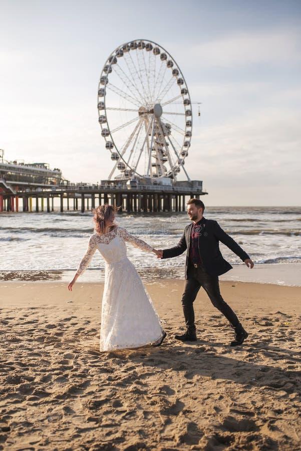 在海滩的日落期间年轻和美好的已婚夫妇庆祝他们的婚礼 免版税库存图片