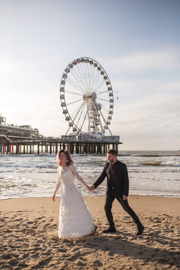 在海滩的日落期间年轻和美好的已婚夫妇庆祝他们的婚礼 库存图片
