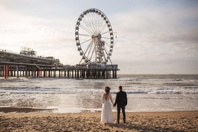 在海滩的日落期间年轻和美好的已婚夫妇庆祝他们的婚礼 库存照片