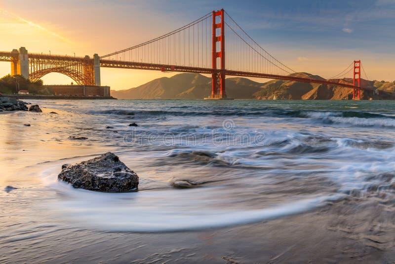 在海滩的日落金门大桥在旧金山C 免版税库存照片