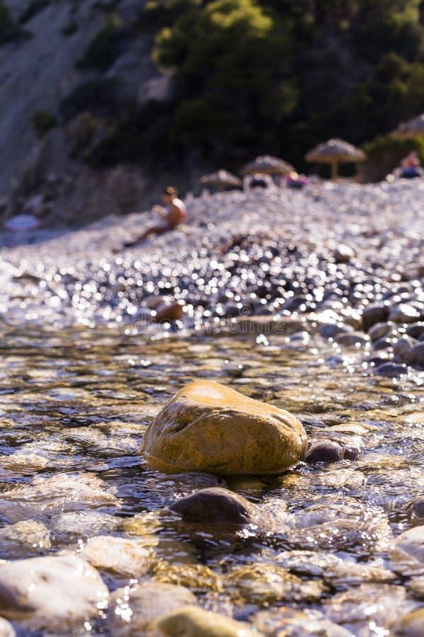 在海滩的日落 盖在岸的水岩石 背景的人们 夏天,假日 ibiza 库存照片