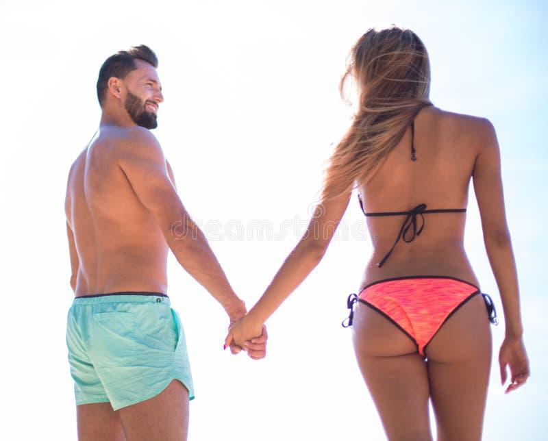 在海滩的有吸引力的适合夫妇在握手的游泳衣 库存照片