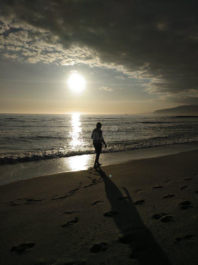 在海滩的步行在孑然 免版税库存图片