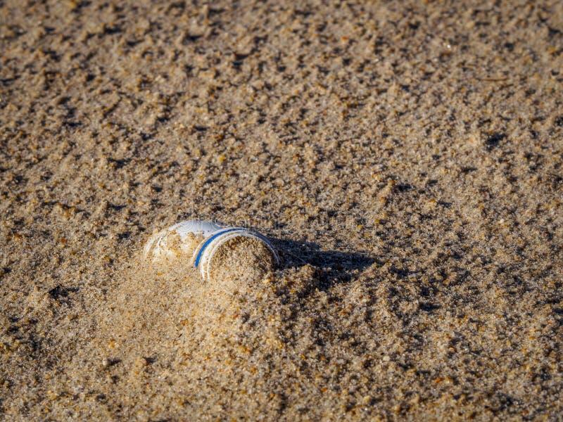 在海滩的沙子塑料埋没的瓶 免版税库存图片