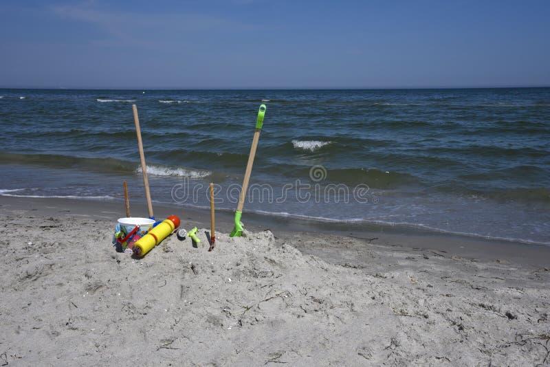 在海滩的沙子玩具在阳光下 免版税库存照片