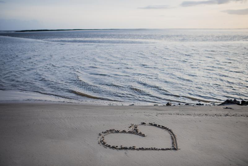 在海滩的沙子画的心脏被海 库存照片