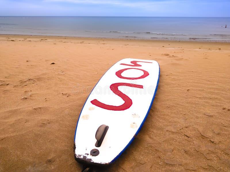 在海滩的沙子的白色冲浪板叫Playa本田-兰萨罗特岛海岛-西班牙 冲浪板在红色显示信件sos 免版税图库摄影