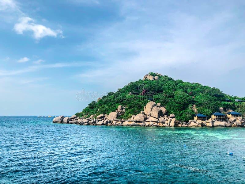 在海滩的清楚的海水有海岛背景 免版税库存图片