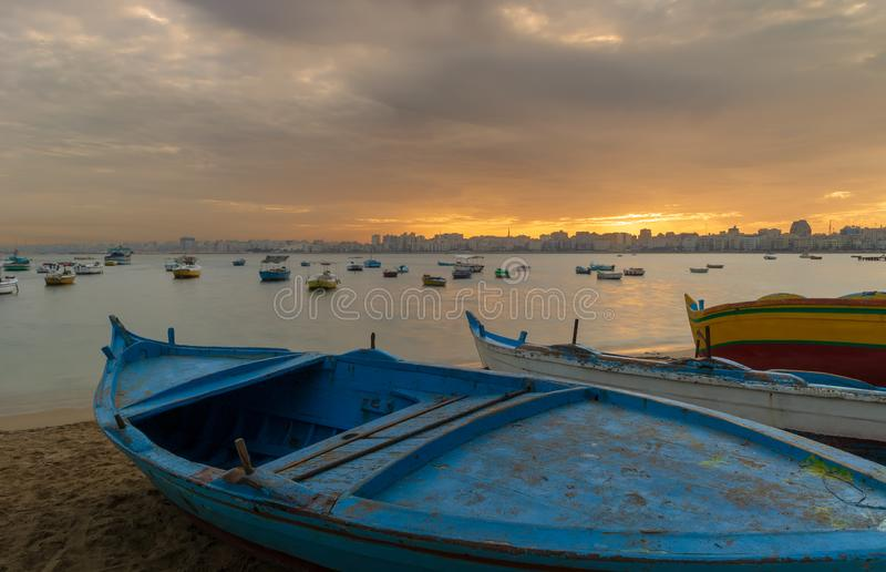 在海滩的渔船在与亚历山大地平线的黄昏在远的距离和五颜六色的天空在日出,埃及 免版税图库摄影