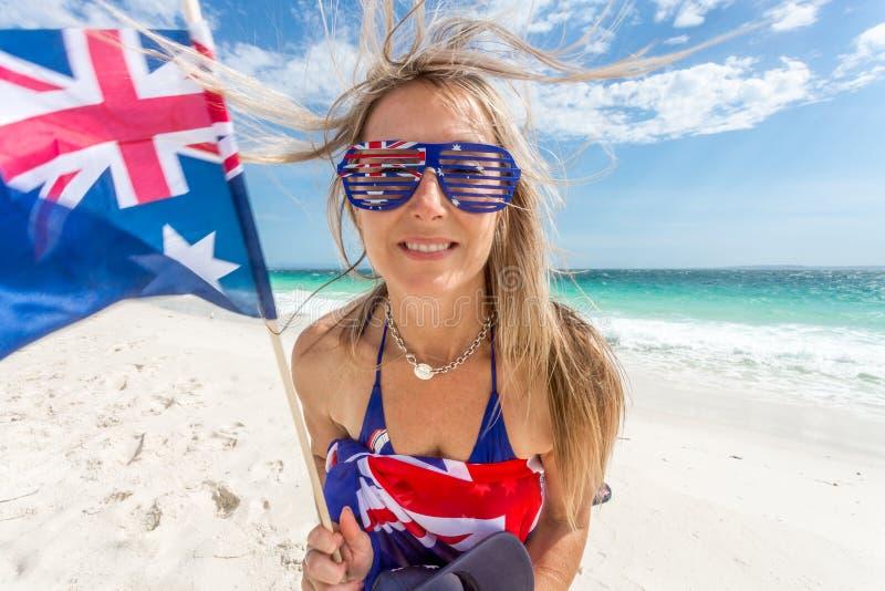 在海滩的澳大利亚支持者或爱好者挥动的旗子 免版税图库摄影
