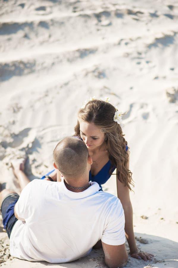 在海滩的爱的夫妇在沙子拥抱 爱的概念和海上的一个日期 库存照片
