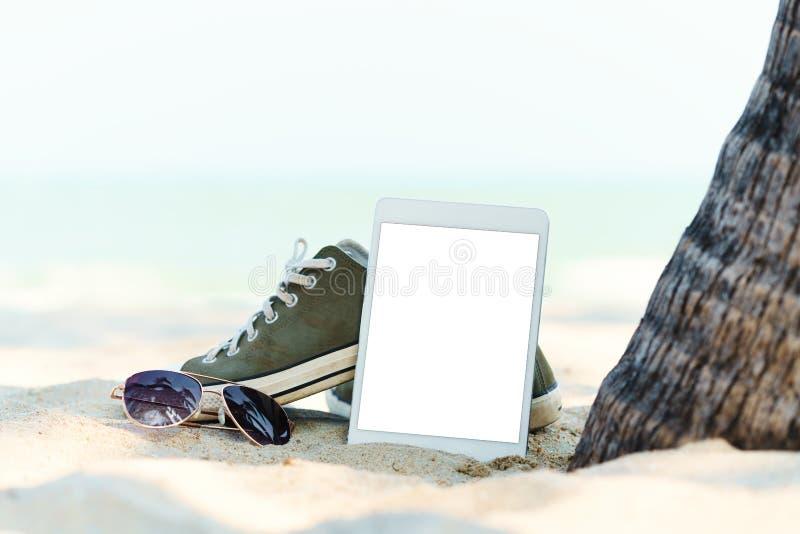 在海滩的特写镜头数字式片剂 库存图片