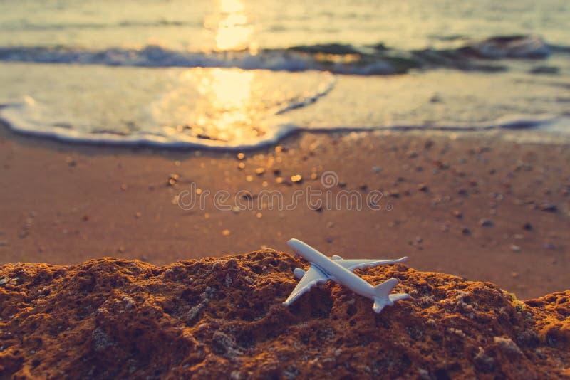在海滩的玩具飞机在日落 旅行和空中运输概念 库存照片