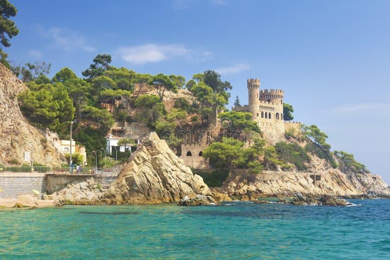在海滩的略雷特德马尔城堡 Sa Caleta海滩的卡斯特尔Platja在加泰罗尼亚西班牙的肋前缘布拉瓦岛 钓鱼地中海净海运金枪鱼的偏差 免版税库存照片
