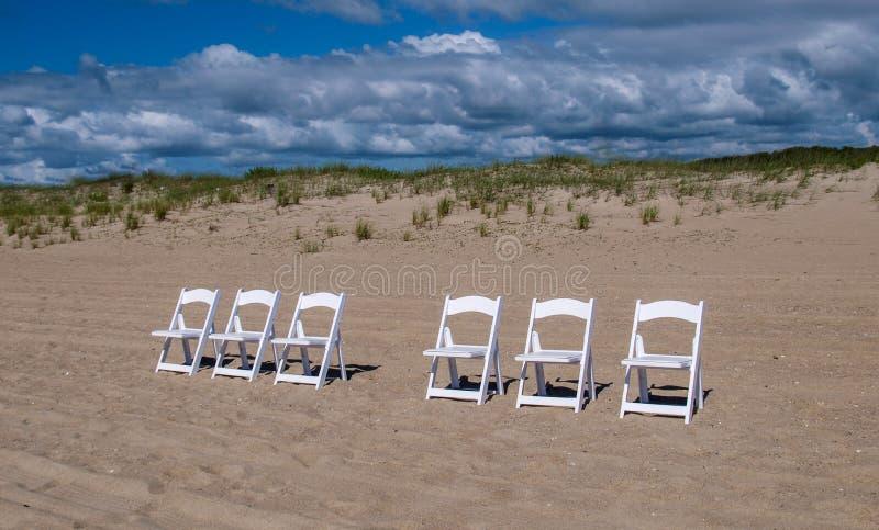 在海滩的白色木椅子 免版税库存照片