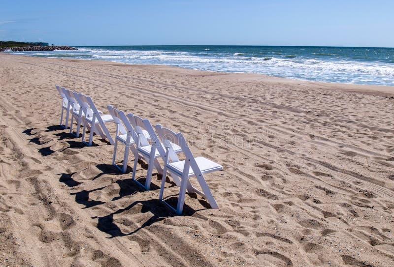 在海滩的白色木椅子 免版税图库摄影