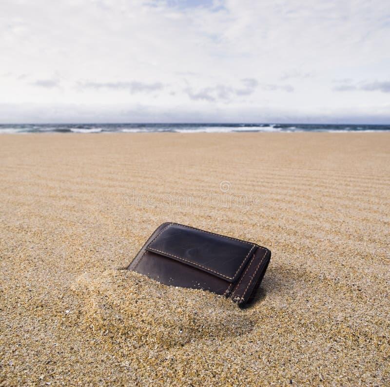 在海滩的皮夹子在沙子 免版税库存图片