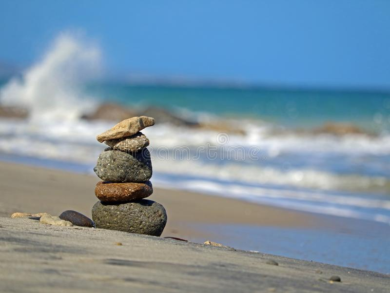 在海滩的石塔楼与波浪在平衡的背景、概念和和谐中 免版税库存图片