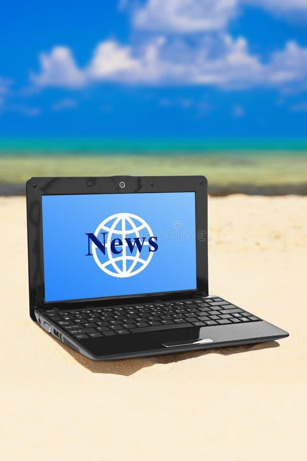 在海滩的笔记本新闻 库存照片