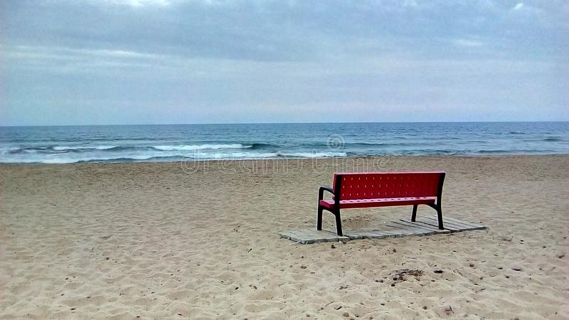 在海滩的红色长凳 库存图片