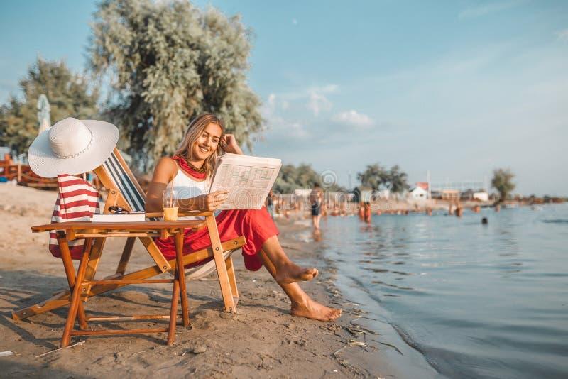 在海滩的美丽的妇女读书报纸 库存照片